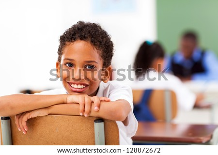 male primary school student in classroom with classmate and teacher
