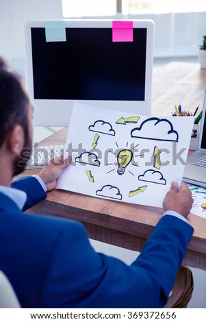 Male professional looking at clouds and bulb drawn on paper at office - stock photo