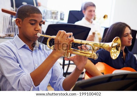 Male Pupil Playing Trumpet In High School Orchestra - stock photo
