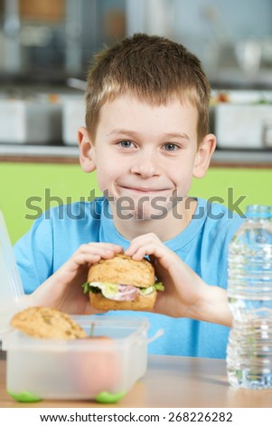 Male Pupil Sitting At Table In School Cafeteria Eating Healthy Packed Lunch - stock photo