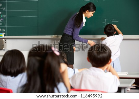 Male Pupil Writing On Blackboard In Chinese School Classroom