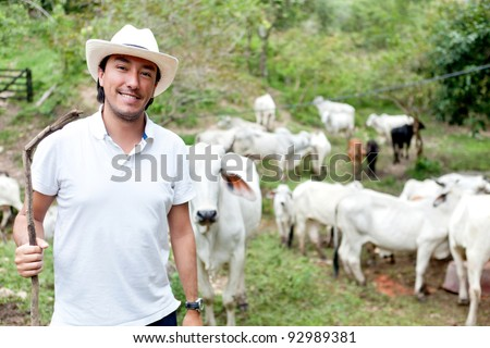 Male rancher in a farm with cattle at the background - stock photo