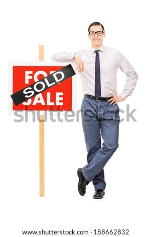 Male real estate agent leaning on a sold sign isolated on white background - stock photo