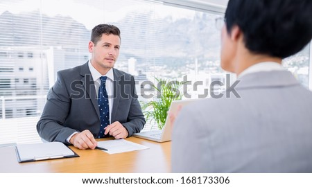 Male recruiter checking the candidate during a job interview at office - stock photo