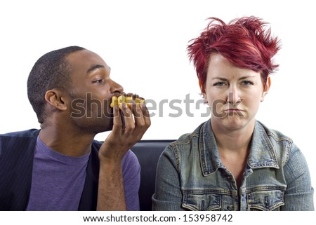 male refusing to share food with female roommate - stock photo
