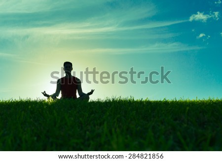 Male relaxing outdoors in the lotus position. - stock photo