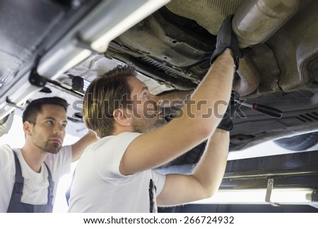 Male repair workers examining car in workshop - stock photo