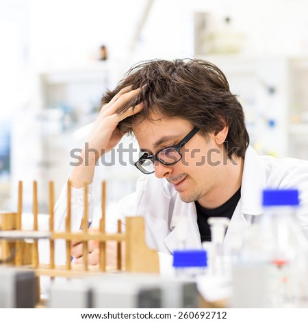 Male researcher carrying out scientific research in a lab (shallow DOF; color toned image) - stock photo