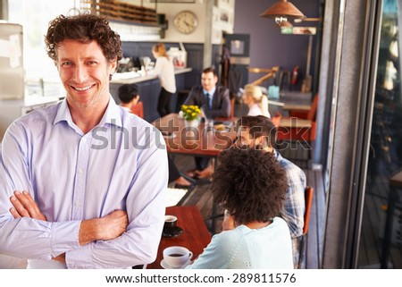 Male restaurant owner, portrait with arms crossed - stock photo