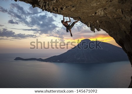 Male rock climber against picturesque view of Telendos Island at sunset. Kalymnos Island, Greece.  - stock photo