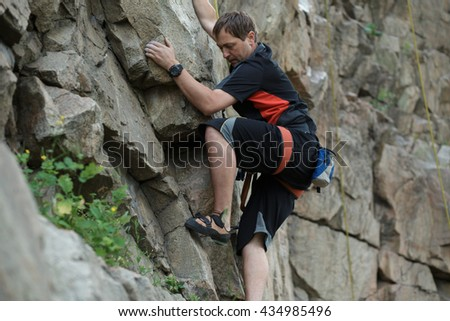 Male rock climber clings to a cliff