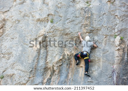 male rock climber struggles for his next grip  - stock photo