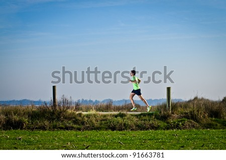Male runner at sprinting speed training for marathon outdoors on country landscape.