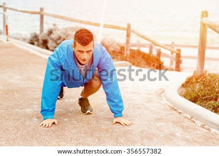 Male runner getting ready to start his race - stock photo