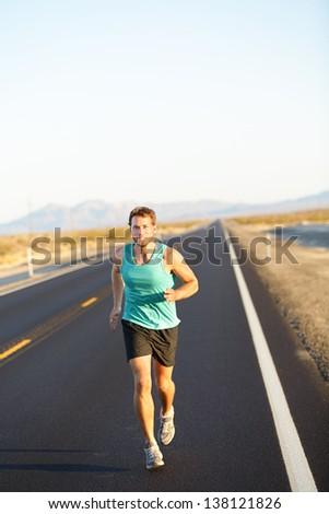 Male runner jogging and running on road in nature landscape. Fit fitness model man working out living healthy lifestyle training for marathon. Young caucasian model in his twenties. - stock photo