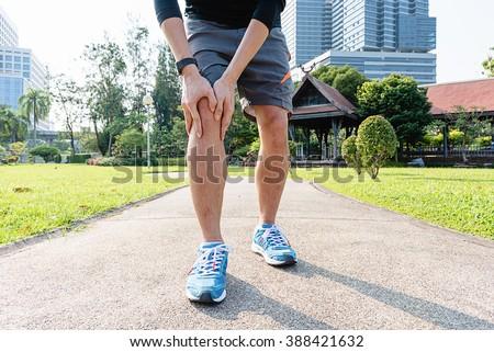 Male runner knee injury and pain - stock photo