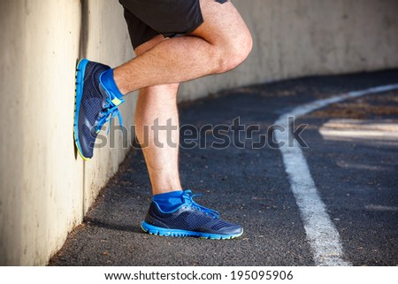 Male runner leaning relaxed against wall. - stock photo
