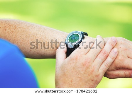 Male runner looking at his heart rate monitor.
