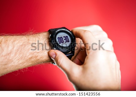 Male runner ready to run with sport watch smartwatch. Taking puls trace or checking gps position wristwatch. Man and fitness, exercising concept on red background - stock photo