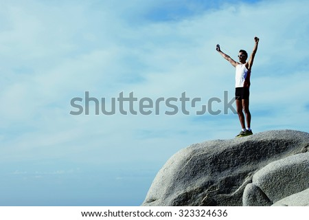 Male runner relaxing after training while standing on stone rock with hands raised against sky background with copy space area for your advertising, fit men celebrating achievement with hands raised - stock photo