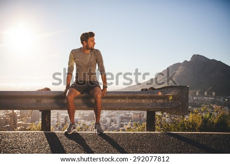 Male runner sitting on a guardrail on country road looking away on sunny day. Young man taking a break after morning run outdoors with bright sunlight. - stock photo