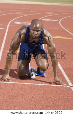 Male runner waiting at the starting block on race track - stock photo