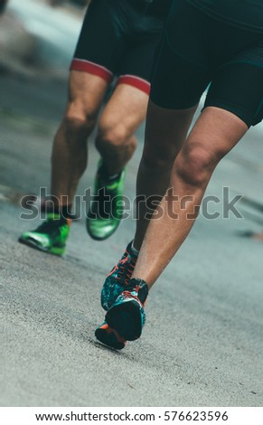 Male runners on the city road.
