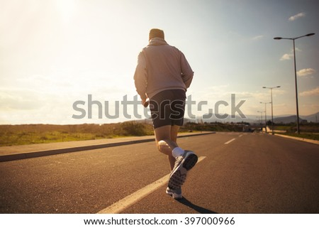 Male running on the road. From the back. Selective focus - stock photo