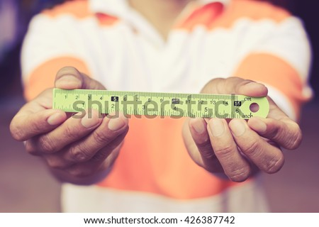 male's hand holding ruler