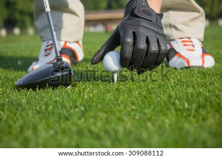 Male's hand in leather glove placing a tee with golf ball isolated on green field background. Golf ball and stick with golfer legs on background.