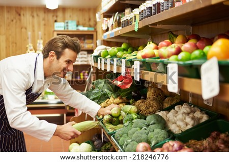 Male Sales Assistant At Vegetable Counter Of Farm Shop - stock photo