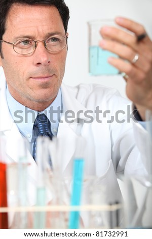 Male scientist holding glass beaker - stock photo