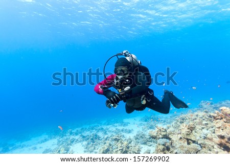 Male scuba diver swimming under water - stock photo