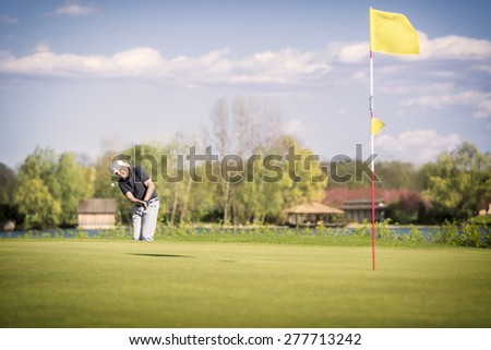 Male senior golf player shooting onto green, with flag in hole in foreground. - stock photo