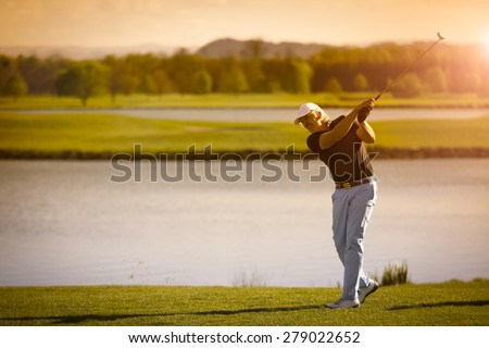 Male senior golf player swinging golf club with lake in background at sunset with copyspace. - stock photo