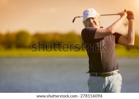 Male senior golf player swinging golf club with lake in background at sunset with sunflare. - stock photo