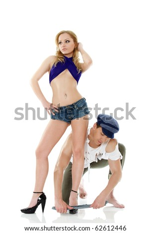 Male shoe shiner cleaning a young woman sandals - stock photo