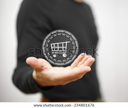 Male showing virtual shopping cart on palm, shopping concept - stock photo