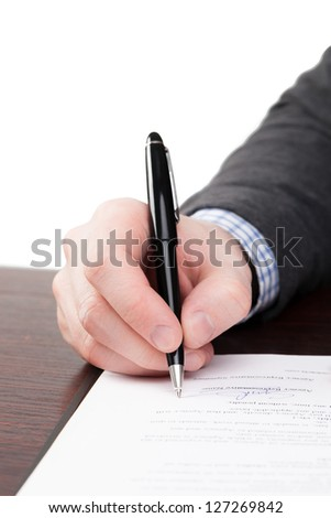 Male signing documents with black pen on a desk - stock photo
