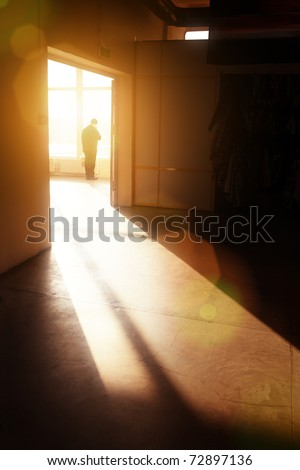 Male silhouette in empty interior looking in window, lit by dramatic sunlight. - stock photo