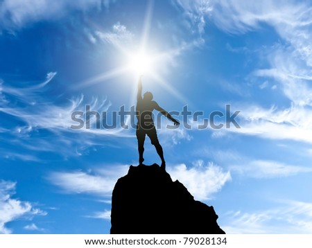 male silhouette on top of the mountain reaches for the sun