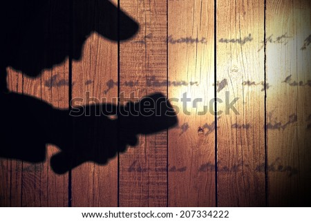 Male silhouette with searchlight on wooden wall  with unrecognizable text. You can see more silhouettes and crime scene in my set. - stock photo