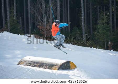 Male skier flying over a hurdle in winter day with forest of firs and ski lifts in background at a winter resort.