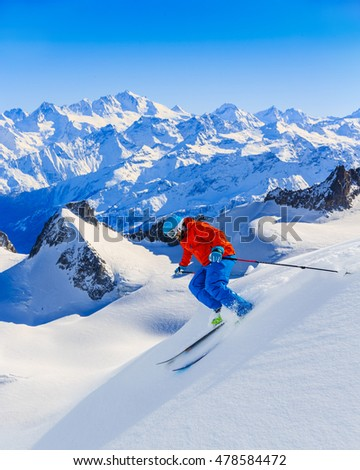 Male skier skiing in fresh snow off ski slope on a sunny winter day at high mountain in French Alps. Freeski in powder snow.