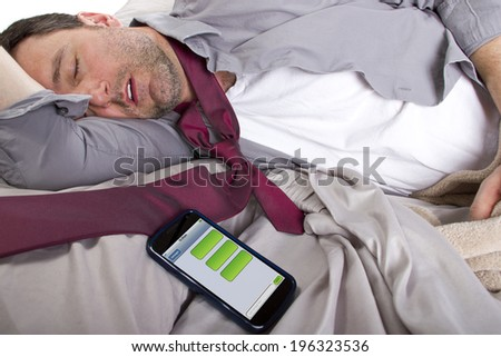 male sleeping in work clothes and receiving text messages from work - stock photo