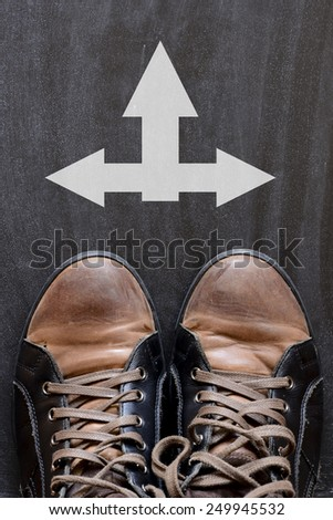 Male sneakers with arrows. Male sneakers on the asphalt road with arrows - stock photo