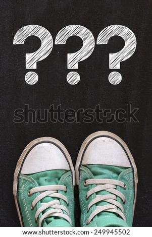 Male sneakers with question marks. Male sneakers on the asphalt road with question marks - stock photo