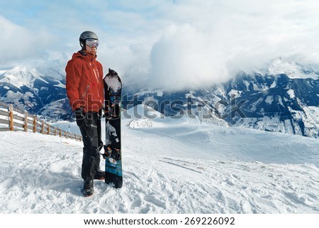 Male snowboarder against panoramic winter mountains background - stock photo