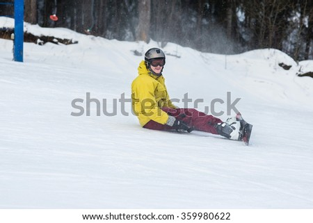 Male snowboarder falls on the slopes during the descent.