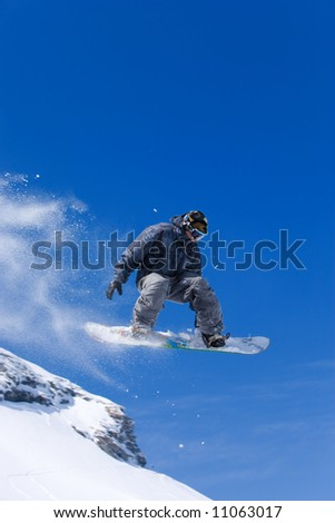 Male snowboarder jumping of a hill - stock photo